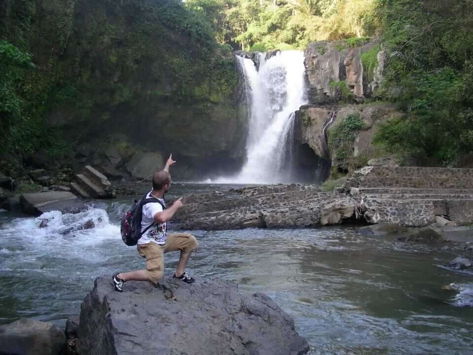 Guy pointing at a waterfall