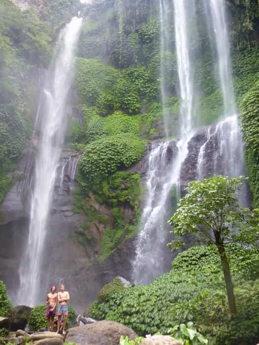 two guys tanding in front of waterfall in bali