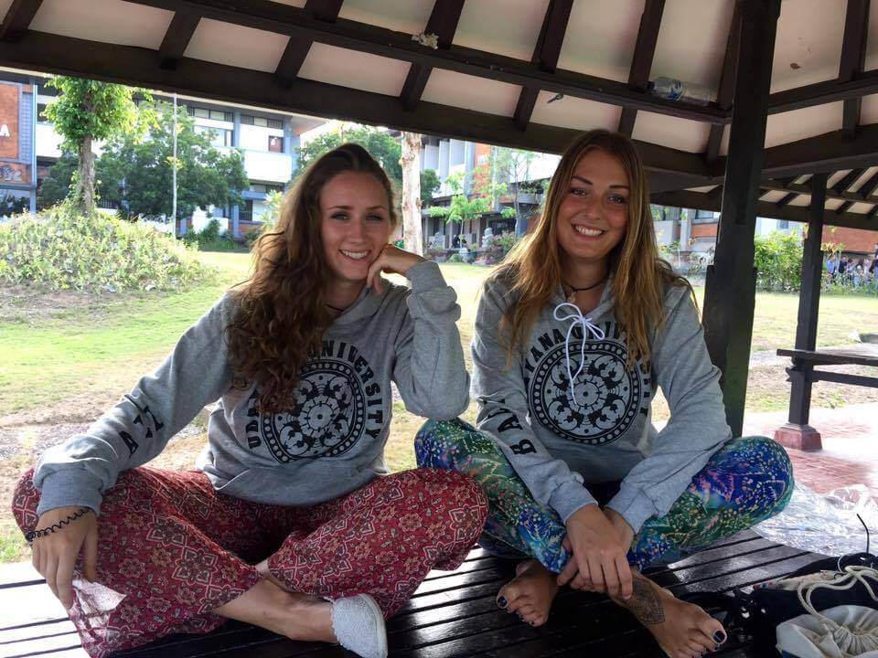 two girls wearing grey hoodie and sits in gazebo in bali indonesia