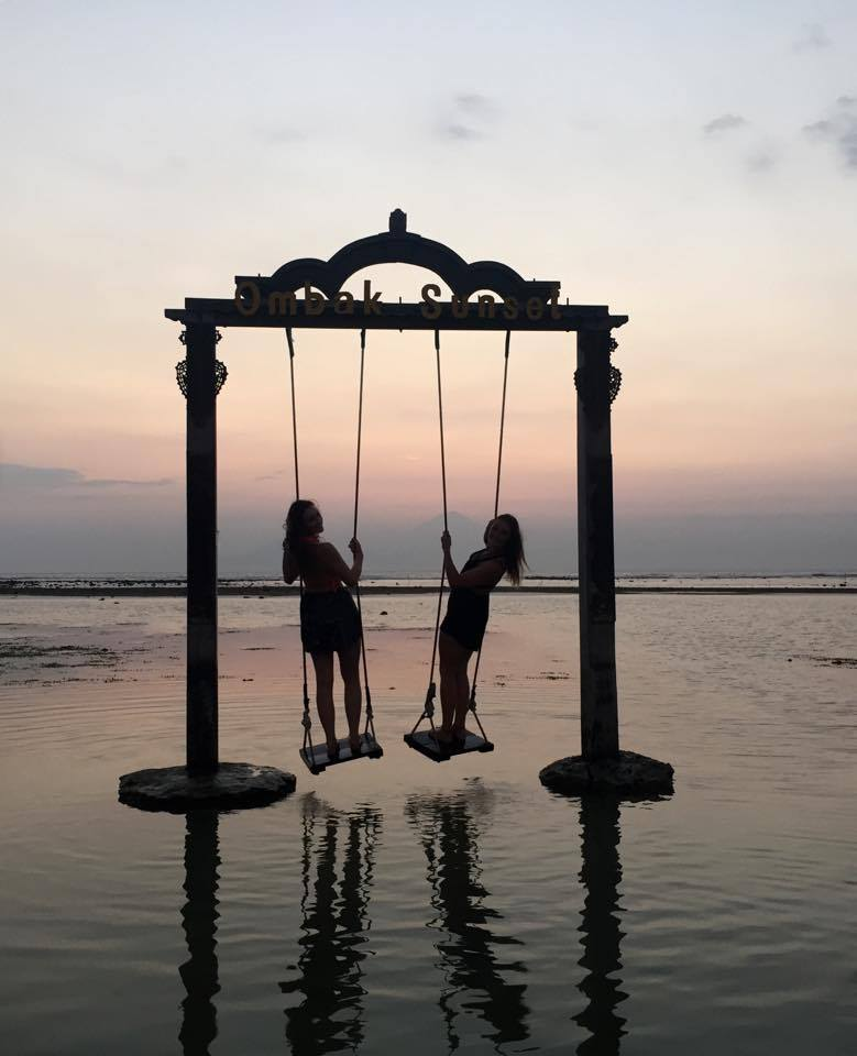 swinging above the ocean in gili island