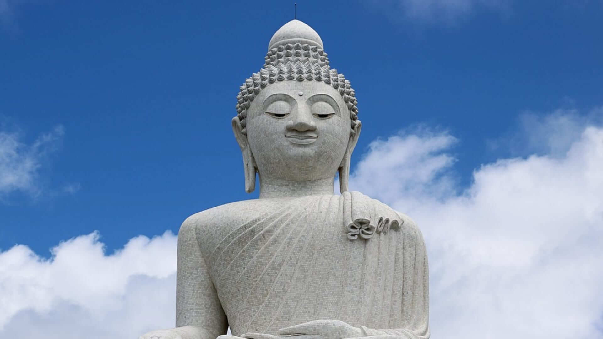 A big white buddha statue and a clear blue sky in Thailand.