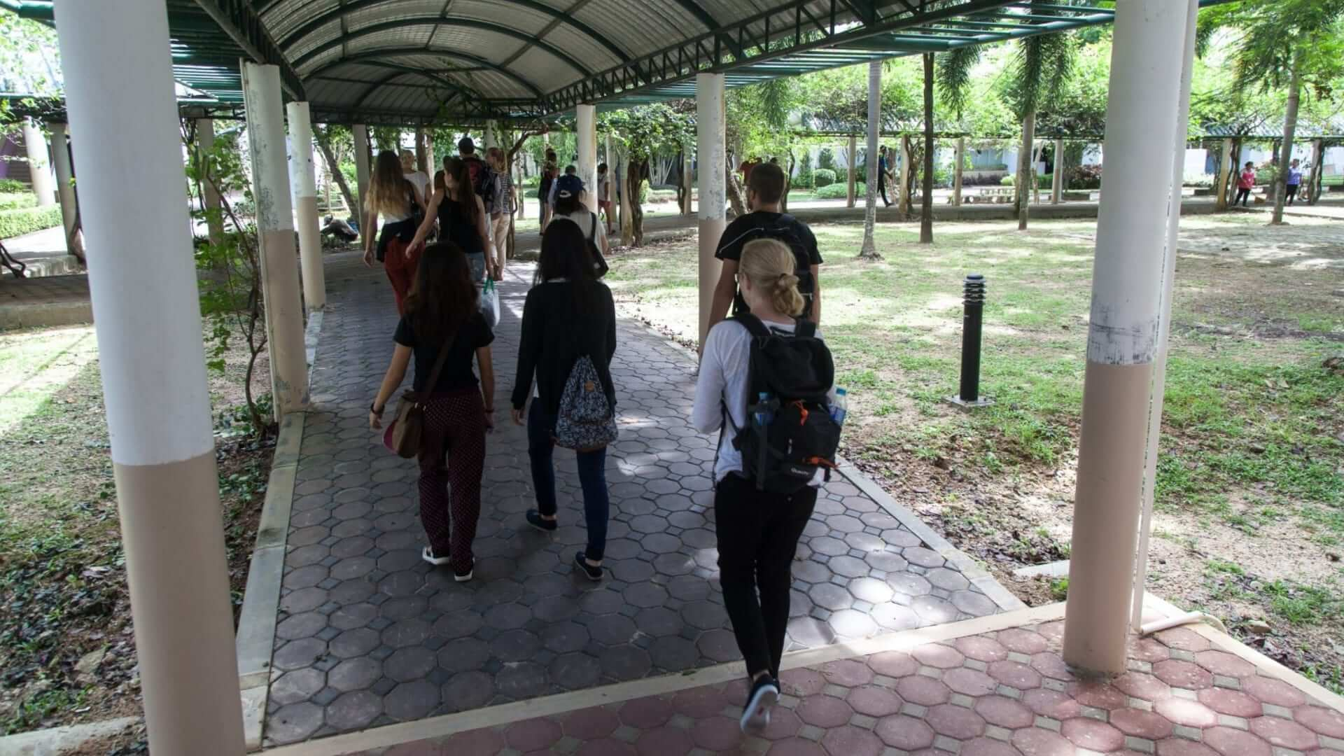 Students are walking on a covered path to school in Thailand.