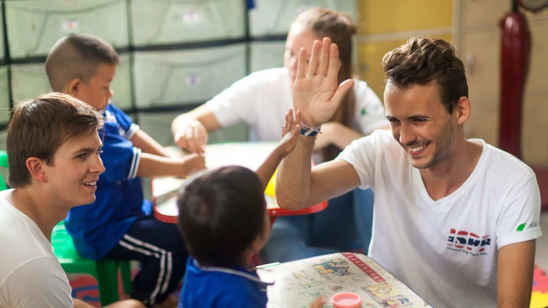 An exchange student is giving a high-five to a Thai child during a charity event in Thailand.