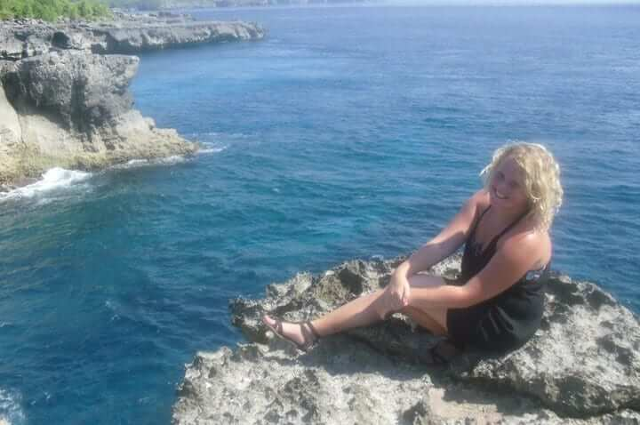Blonde woman sitting on a rock looking over the sea in Bali.
