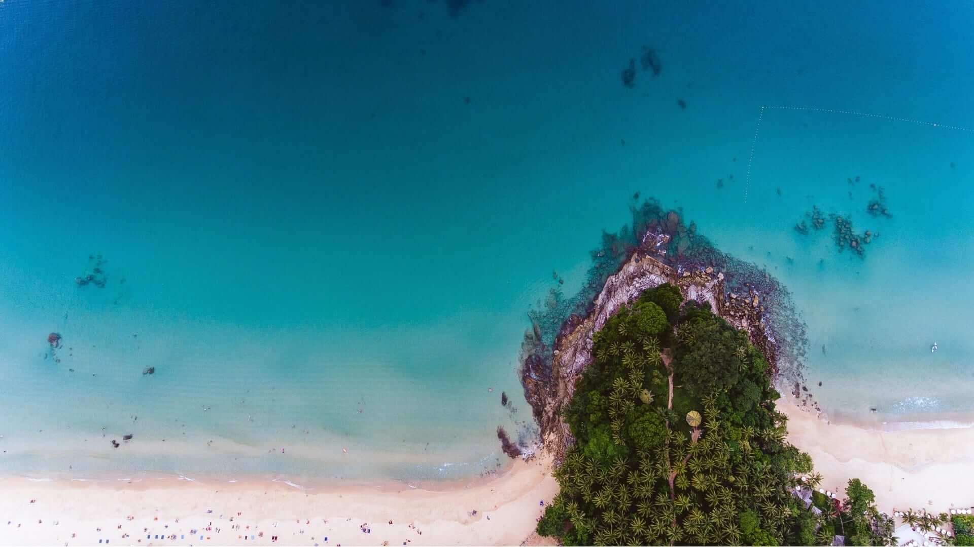A white beach, green trees and a blue ocean in Thailand.