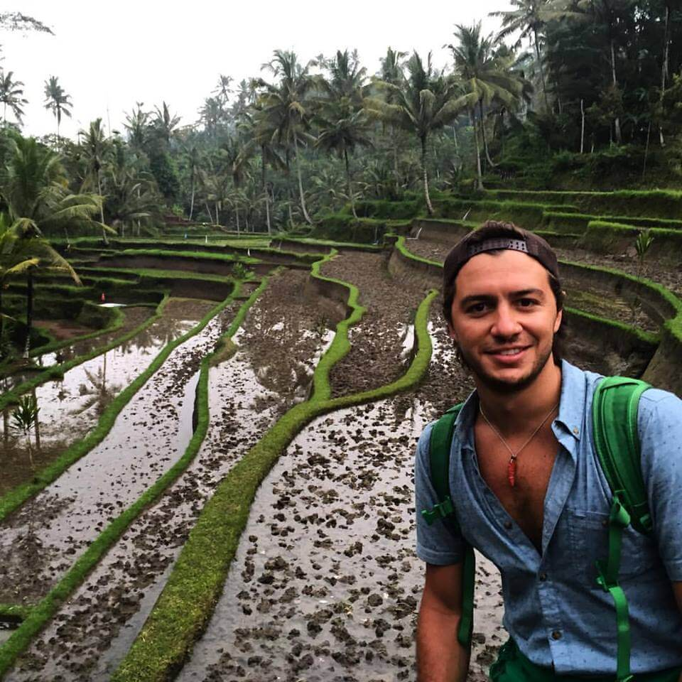 spanish guy smiling in front of rice terrace in bali
