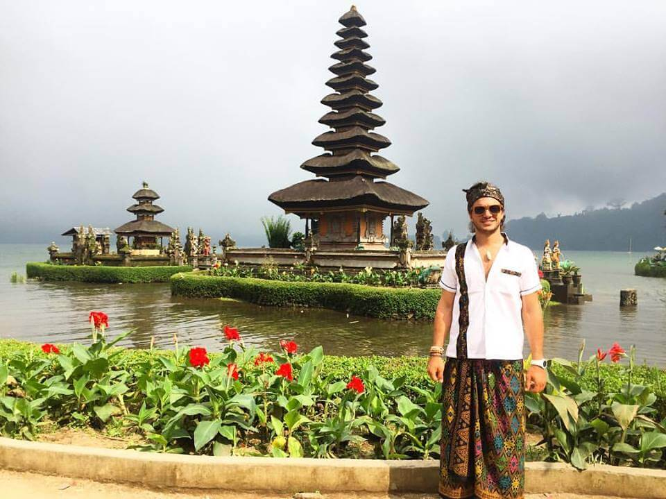 a man standing in front of beratan temple in bali indonesia