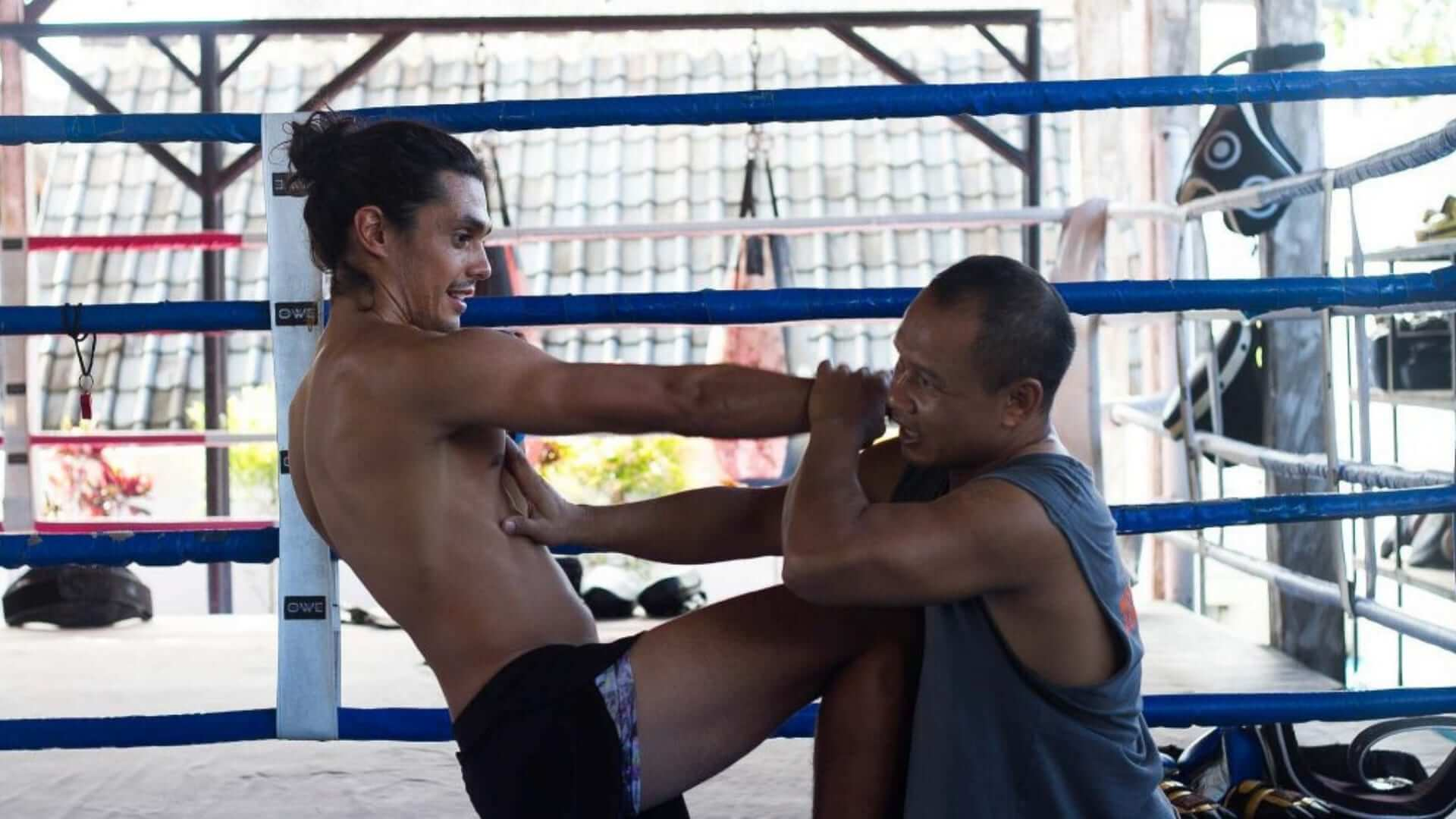 A man is kicking another man during Muay Thai in Thailand.