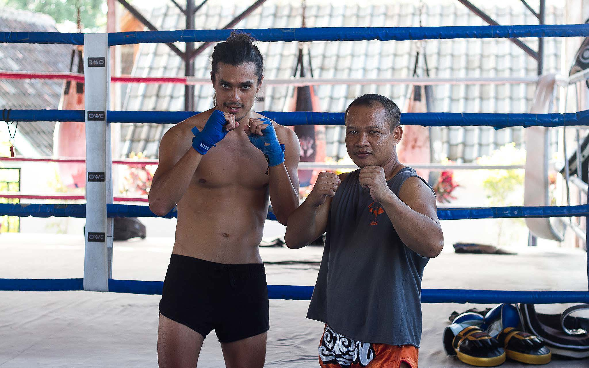 Two man are standing in a boxing position in Thailand.