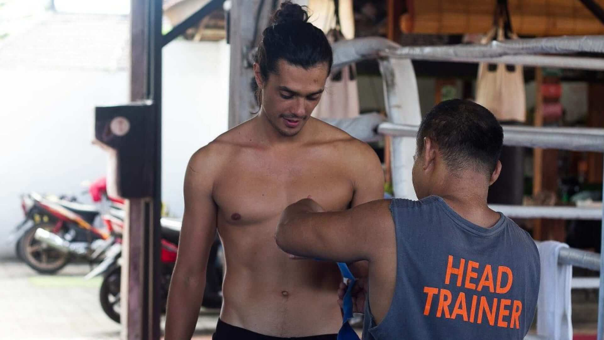 A Muay Thai teacher is explaining someting to another man in Thailand.
