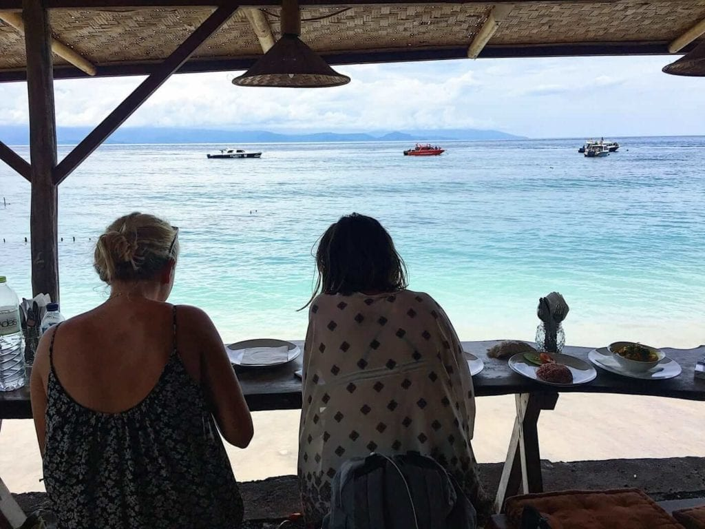 2 girls eating under a hut while viewing the beach in front