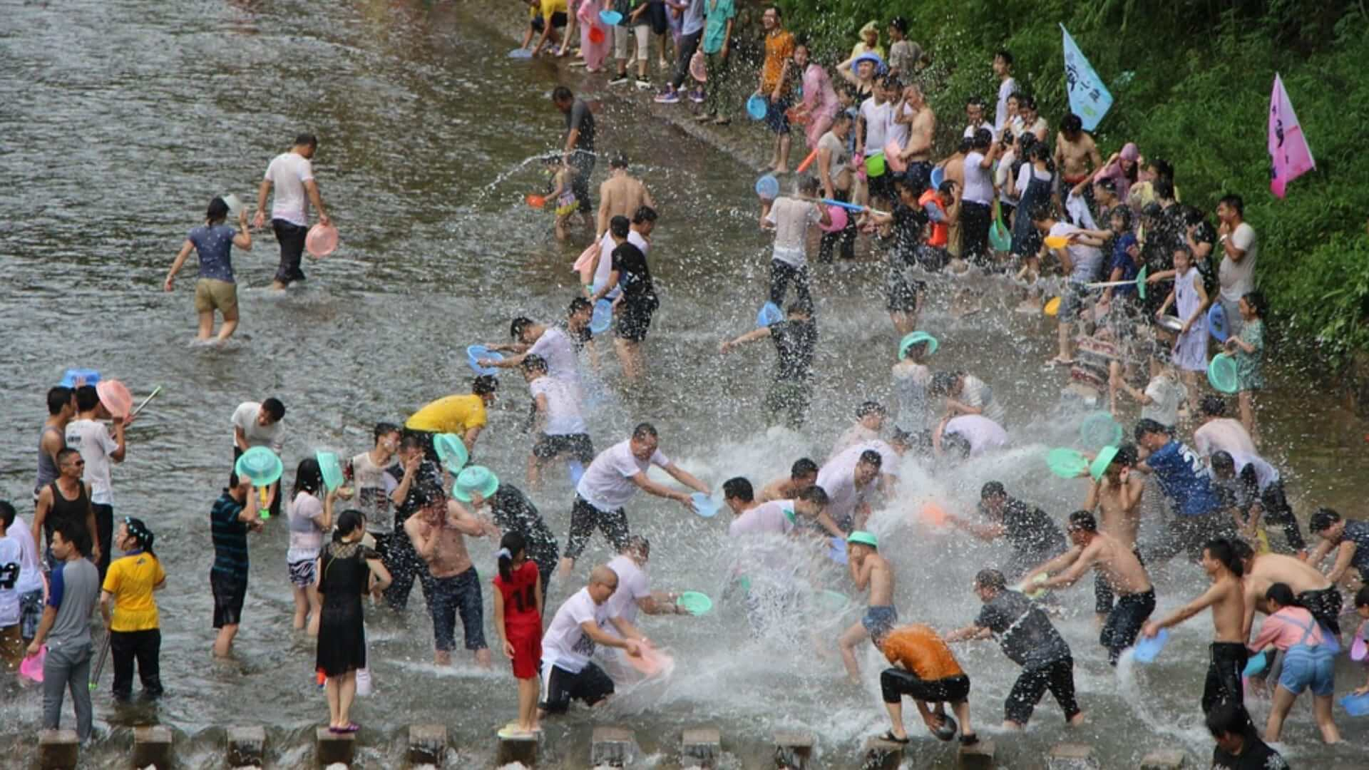 Many people are standing in a river during a water fight in Thailand.