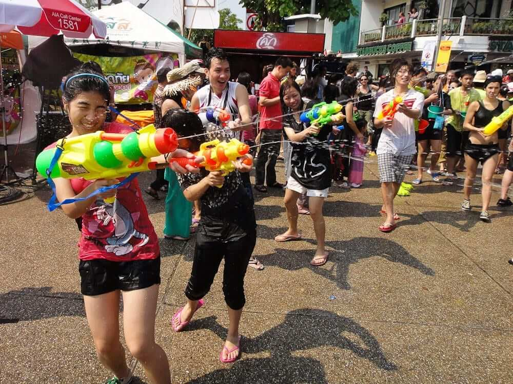 people are having fun while playing with water guns