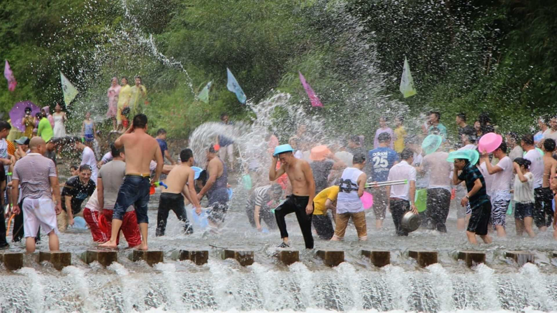 A lot of Thai people are participating in a water fight during a festival in Thailand.