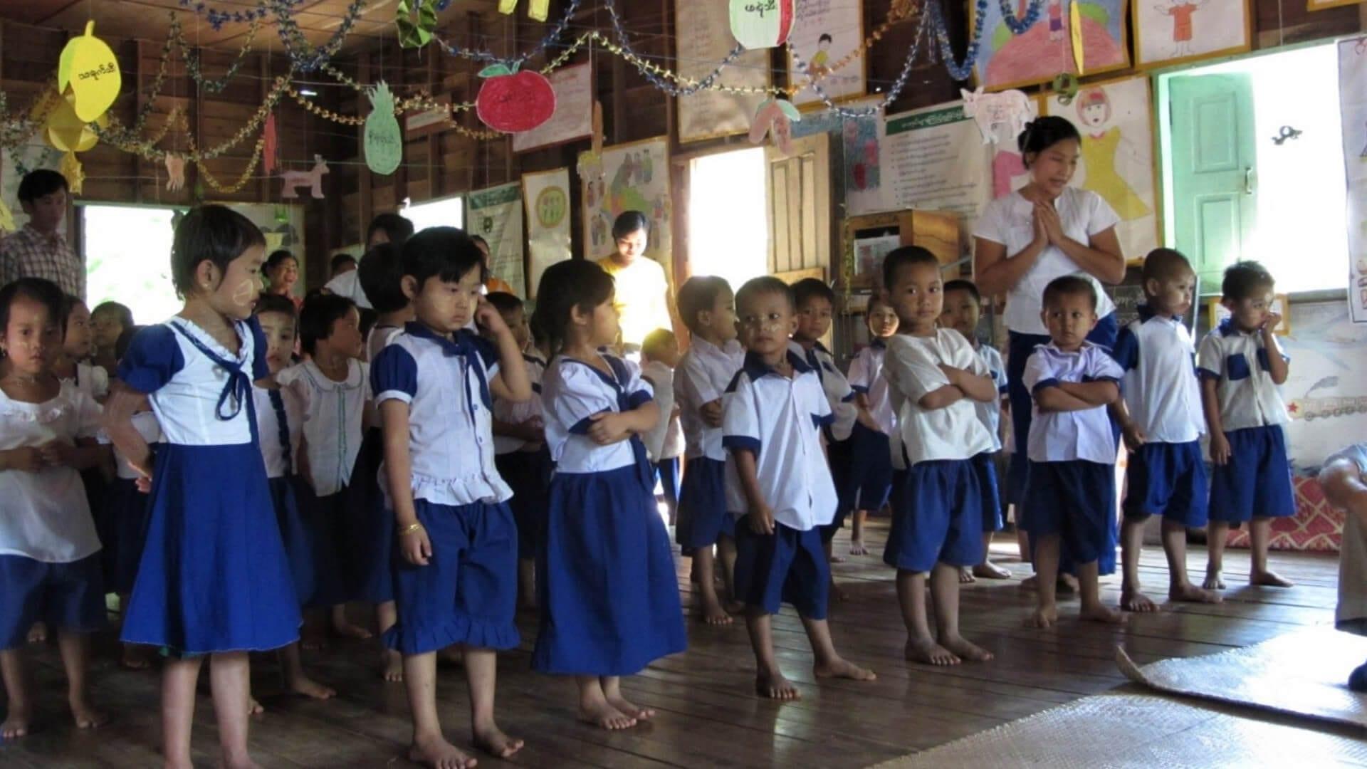 Children in school uniforms are standing in line in Asia.