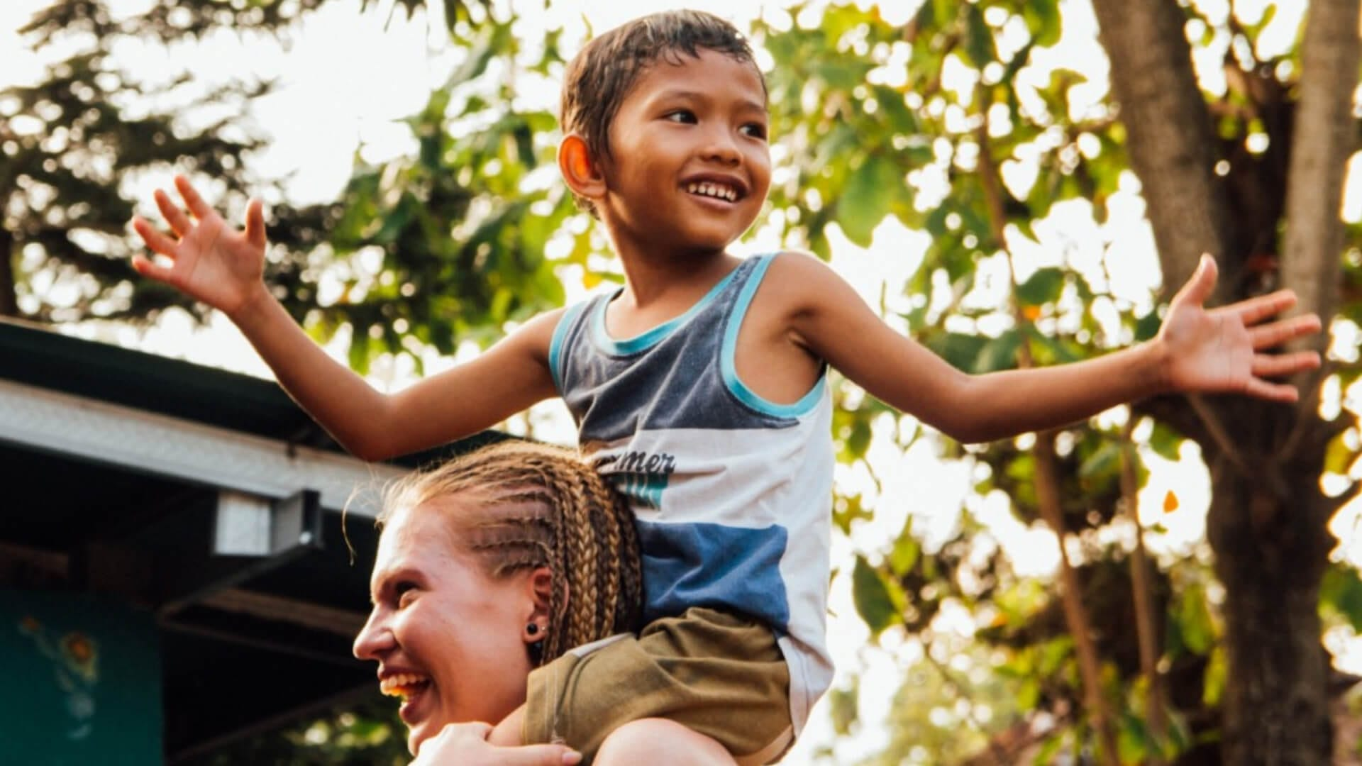 A child is sitting on someone's shoulders and smiling in Asia.