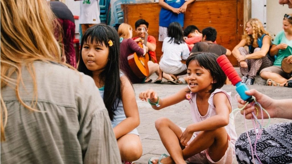 AE students and local children sitting on the ground