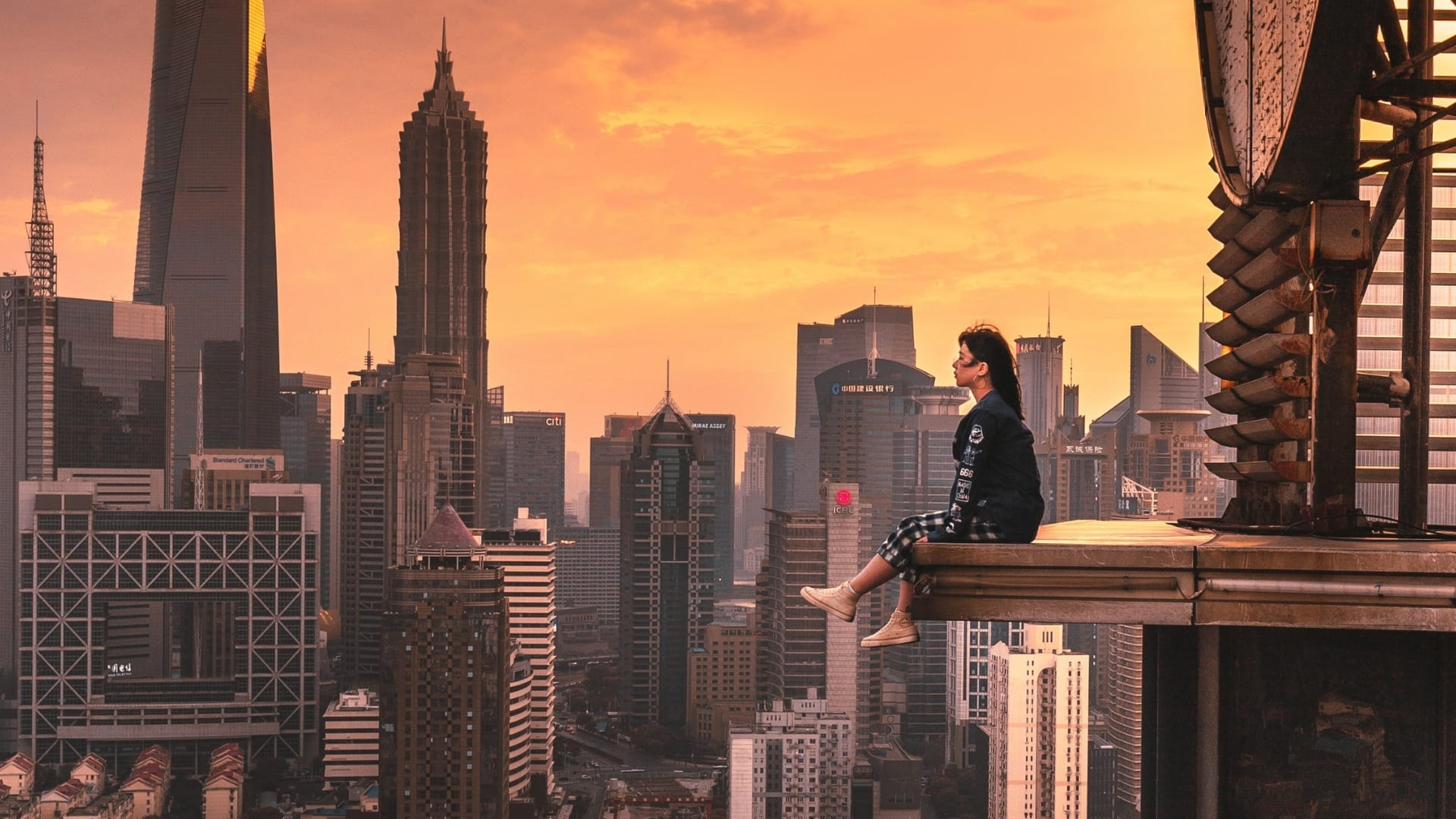 A woman is sitting on a protrusion of a building between other high buildings during sunset in Shanghai.