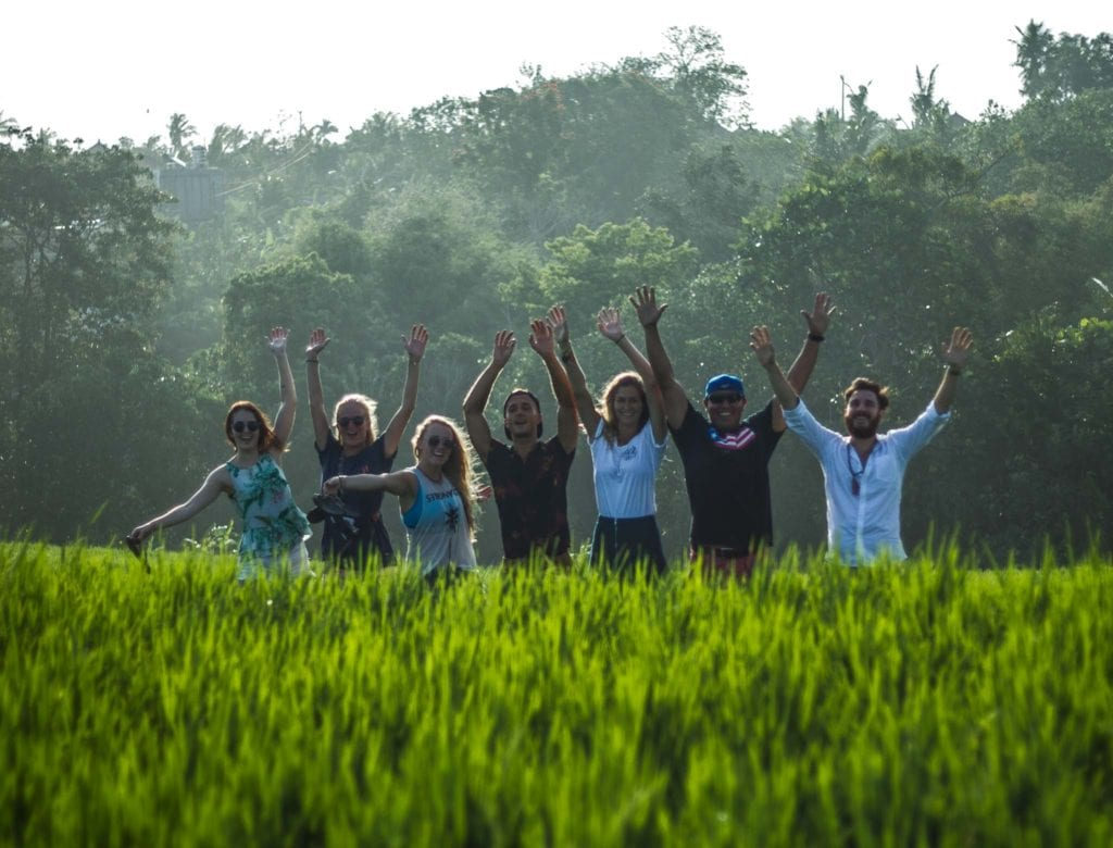 People happily posing for a picture in ricefields