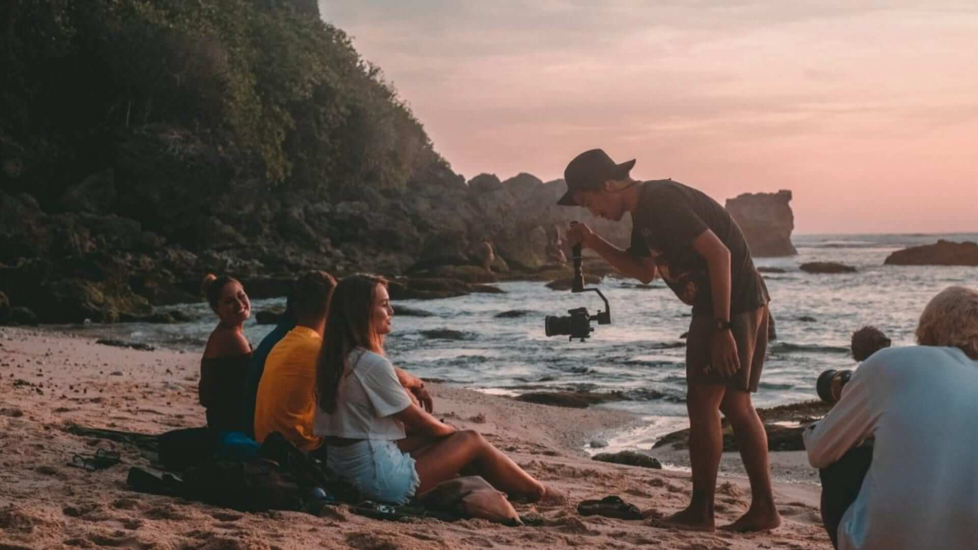 A man is filming students sitting on the beach during sunset in Bali.