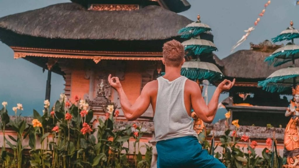 Back view of a boy standing in a yoga position in front of a temple in Bali