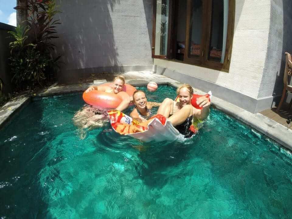 students chilling in mini pool in villa