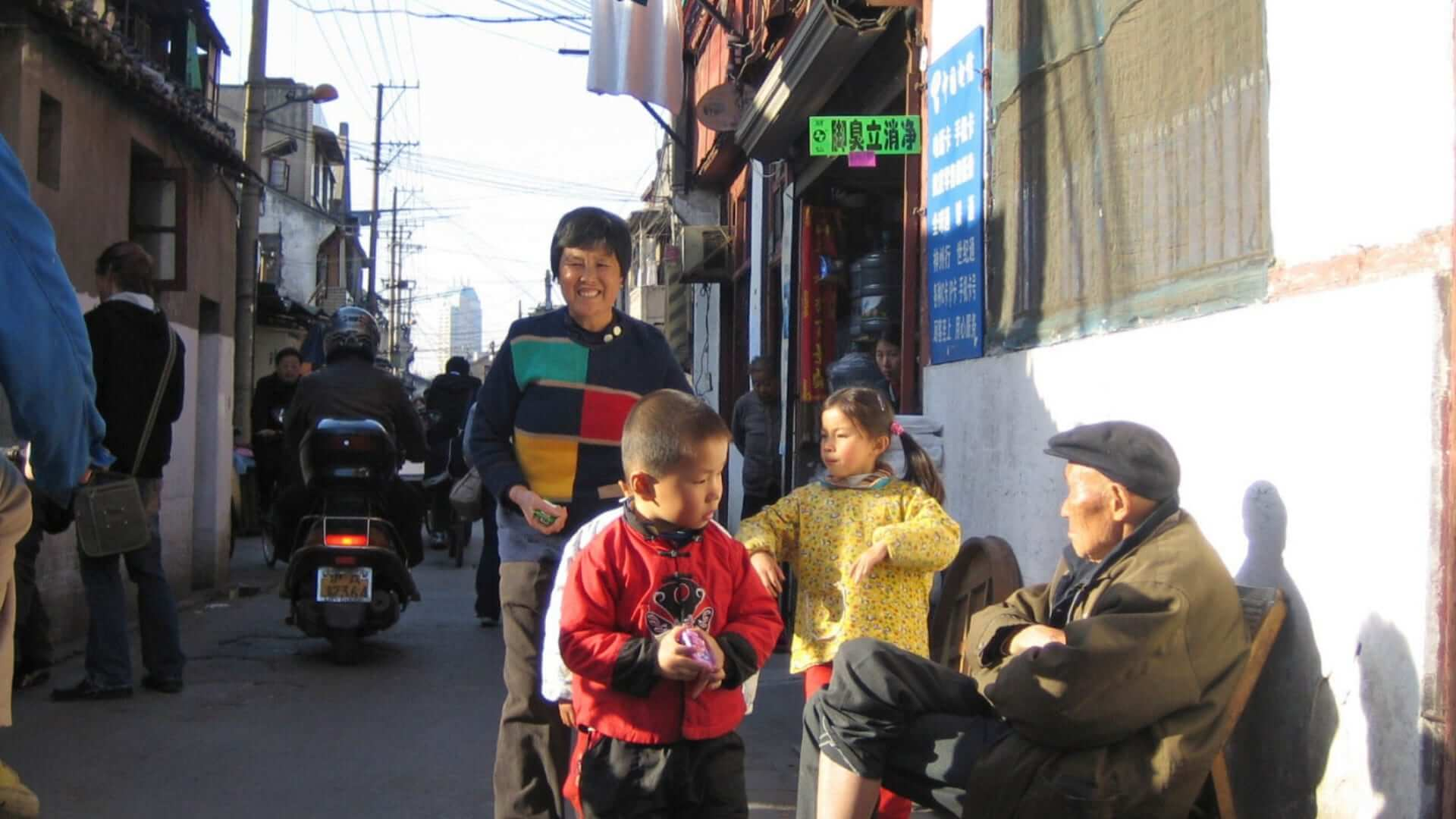 A Chinese woman is smiling and standing in a small street surrounded by other Chinese people in Shanghai.