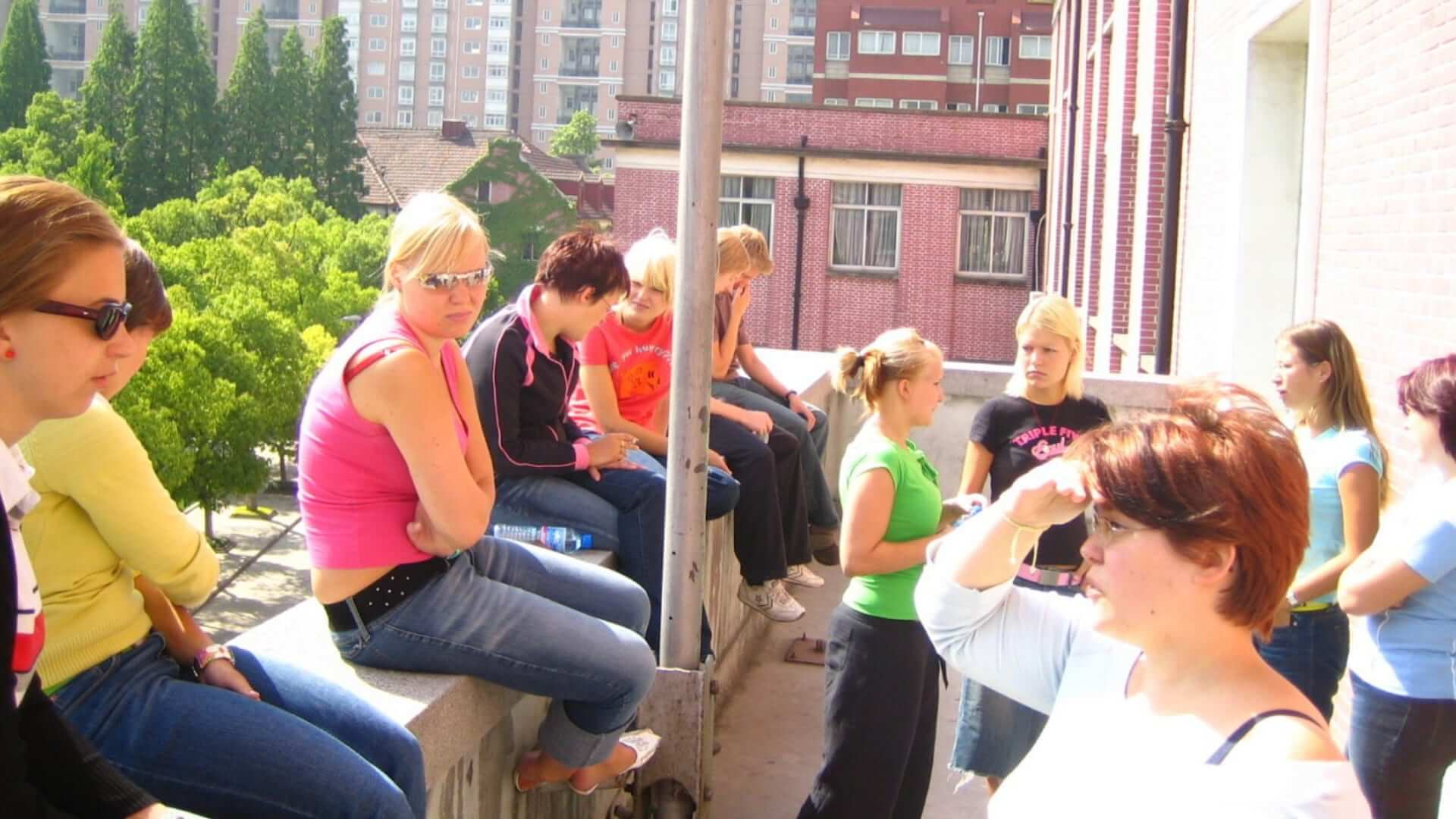 A group of students is sitting and standing on a balcony while they are talking to eachother during sunny weather in Shanghai.