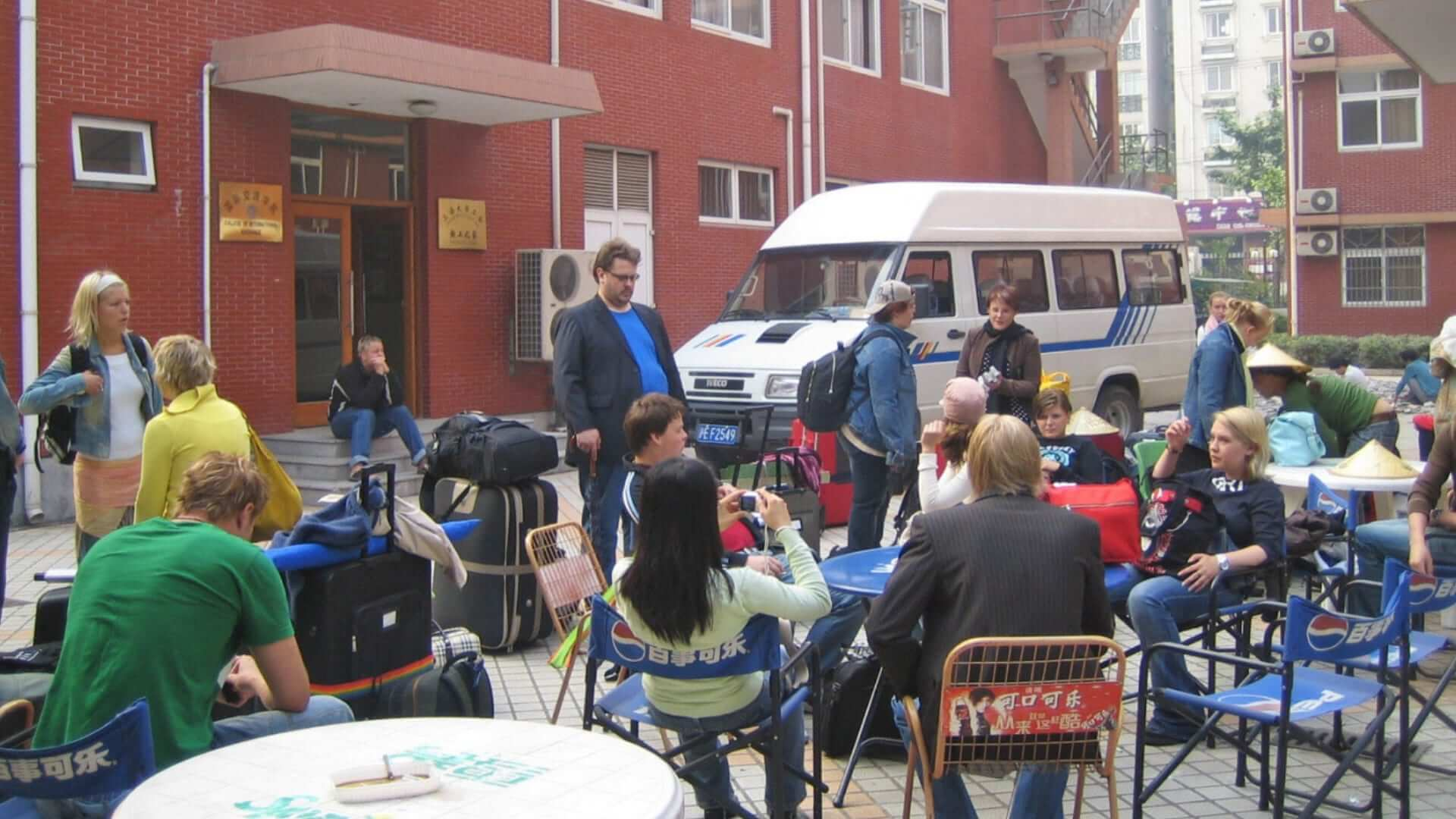 A group of people is sitting outside on a terrace with suitcases waiting in Shanghai.