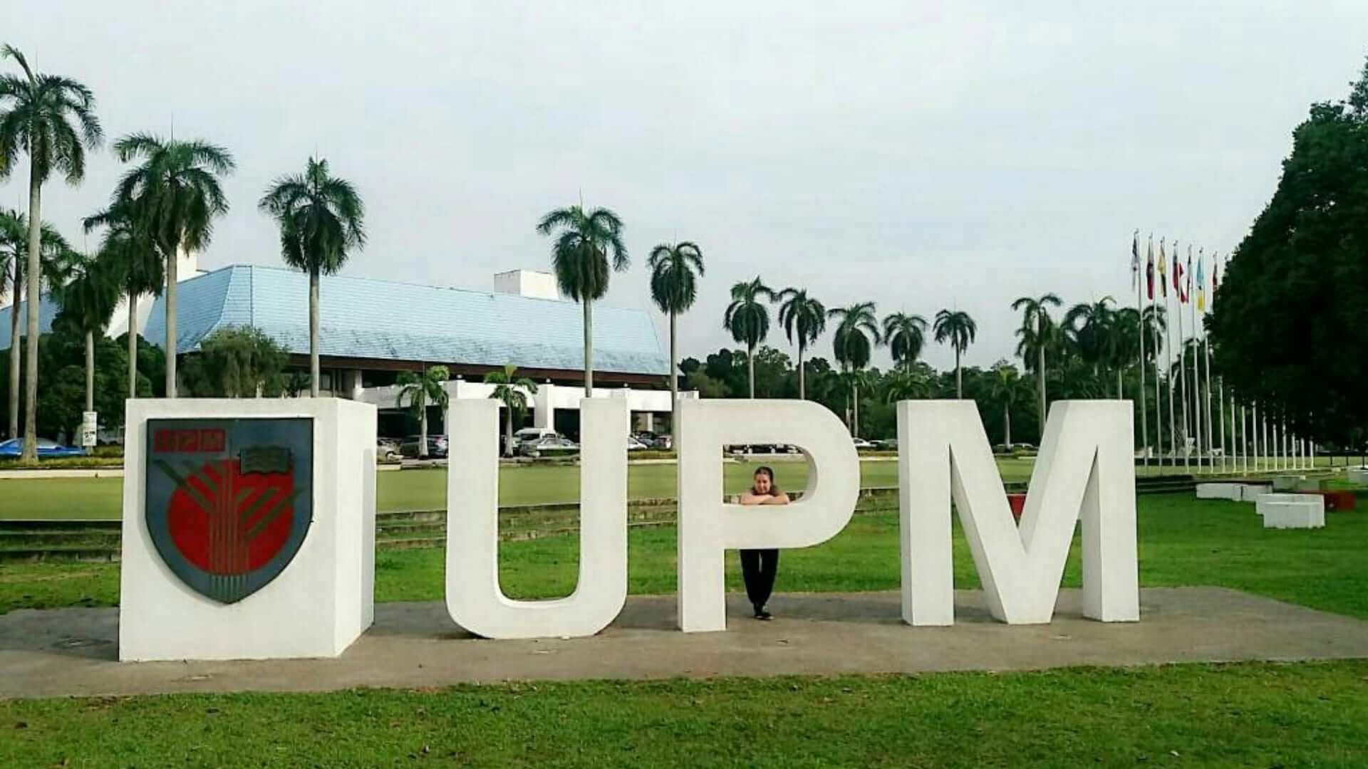 A girl is standing behind white big letters (UPM) on a lawn with palm trees in Malaysia.