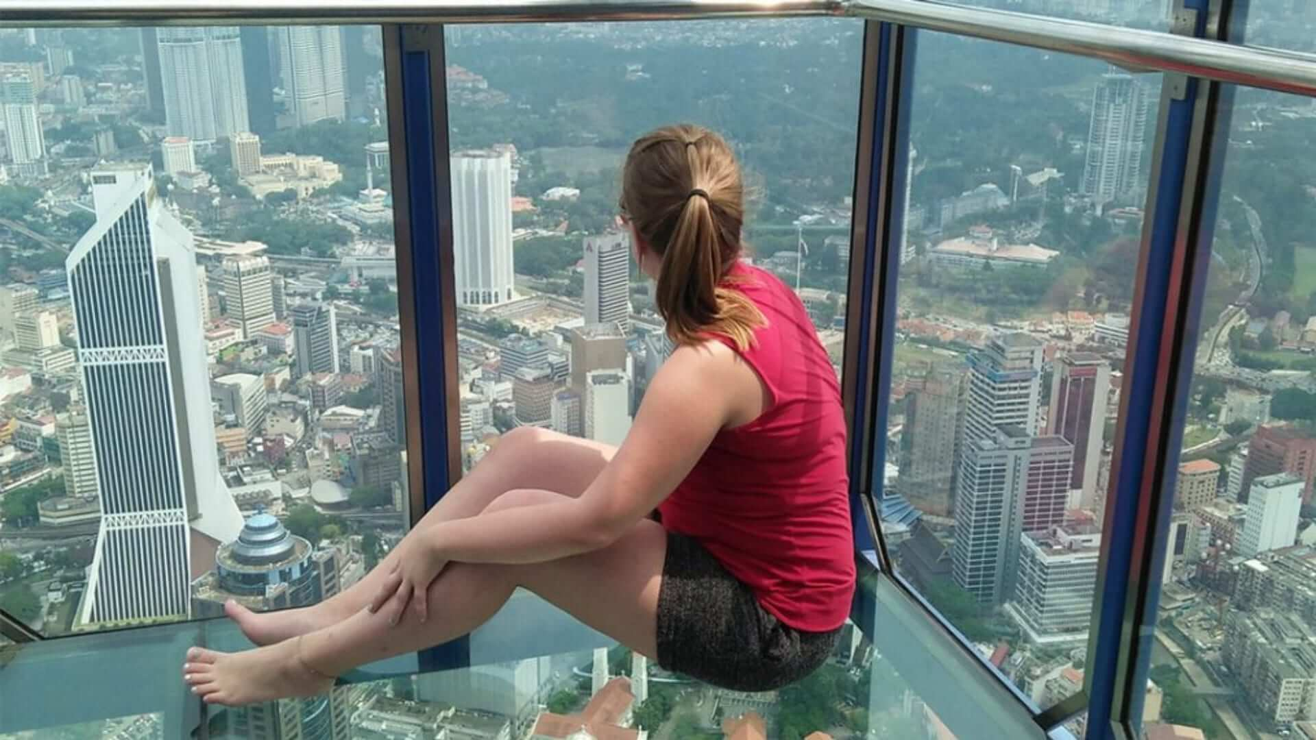 A girl wearing a red top is sitting in a high tower made of glass and looking over the city in Kuala Lumpur.