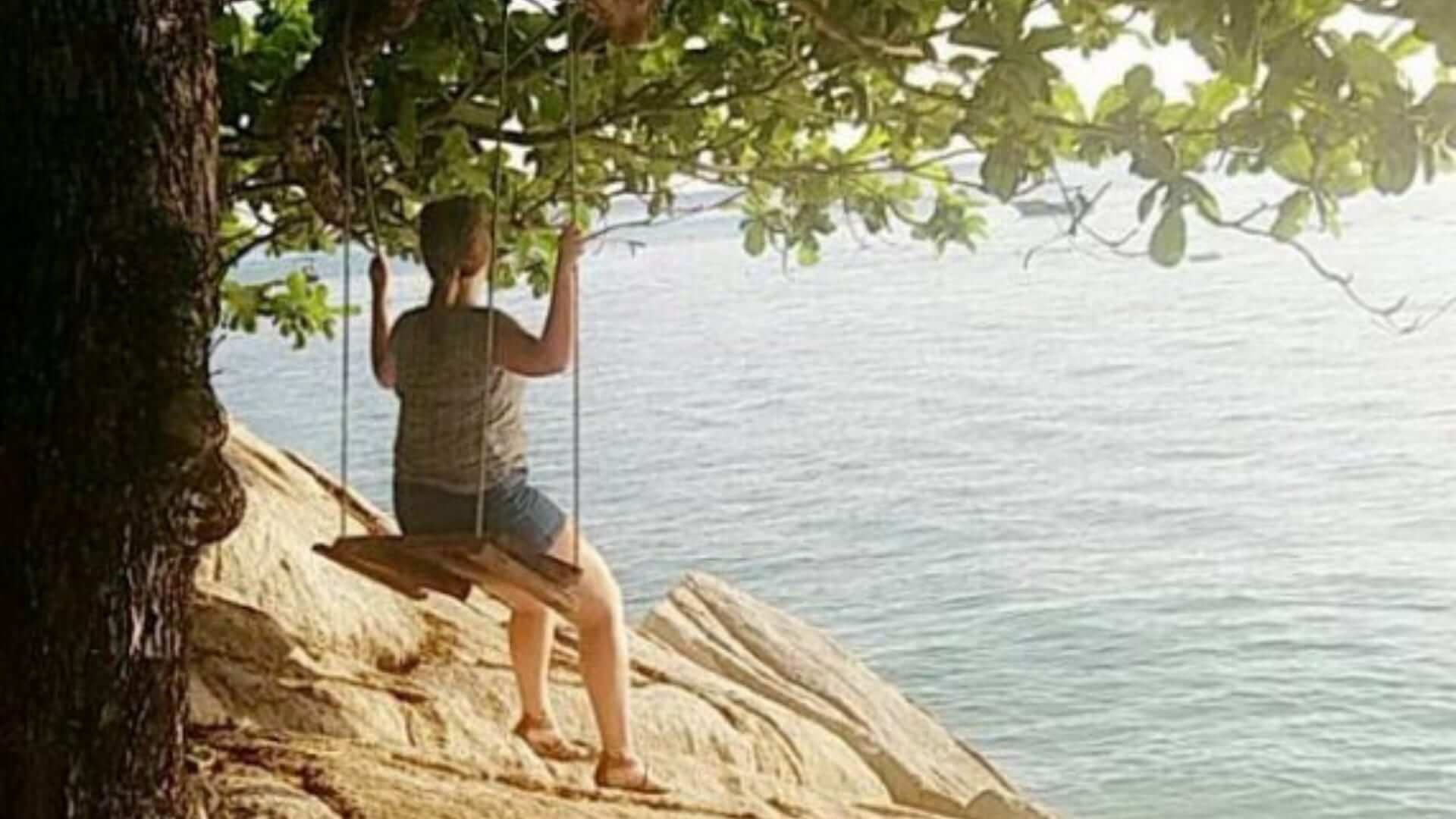 A girl is sitting on a swing under a tree in front of the ocean in Malaysia.