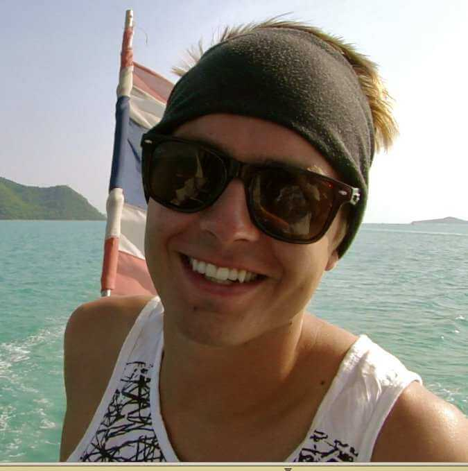 a guy smiling to the camera with thailand flag behind him