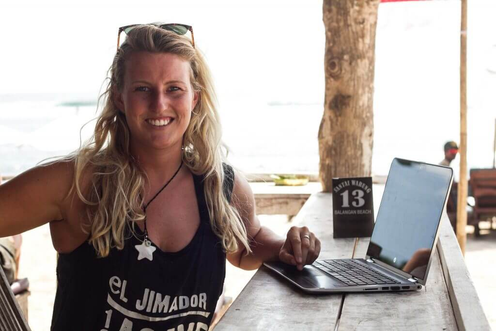 Girl wearing a tank top using her laptop by the beach