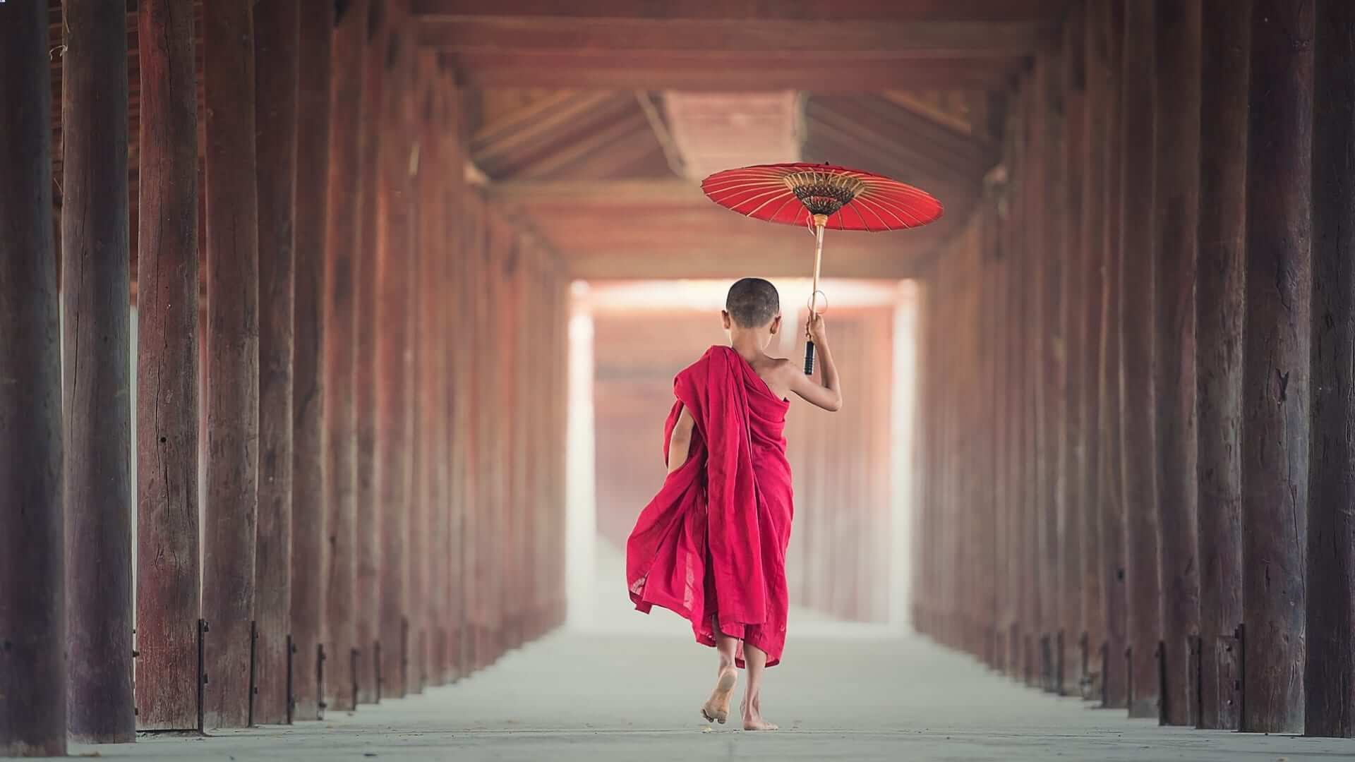 A boy wearing red clothes and holding a red umbrella is walking through a temple in Asia.