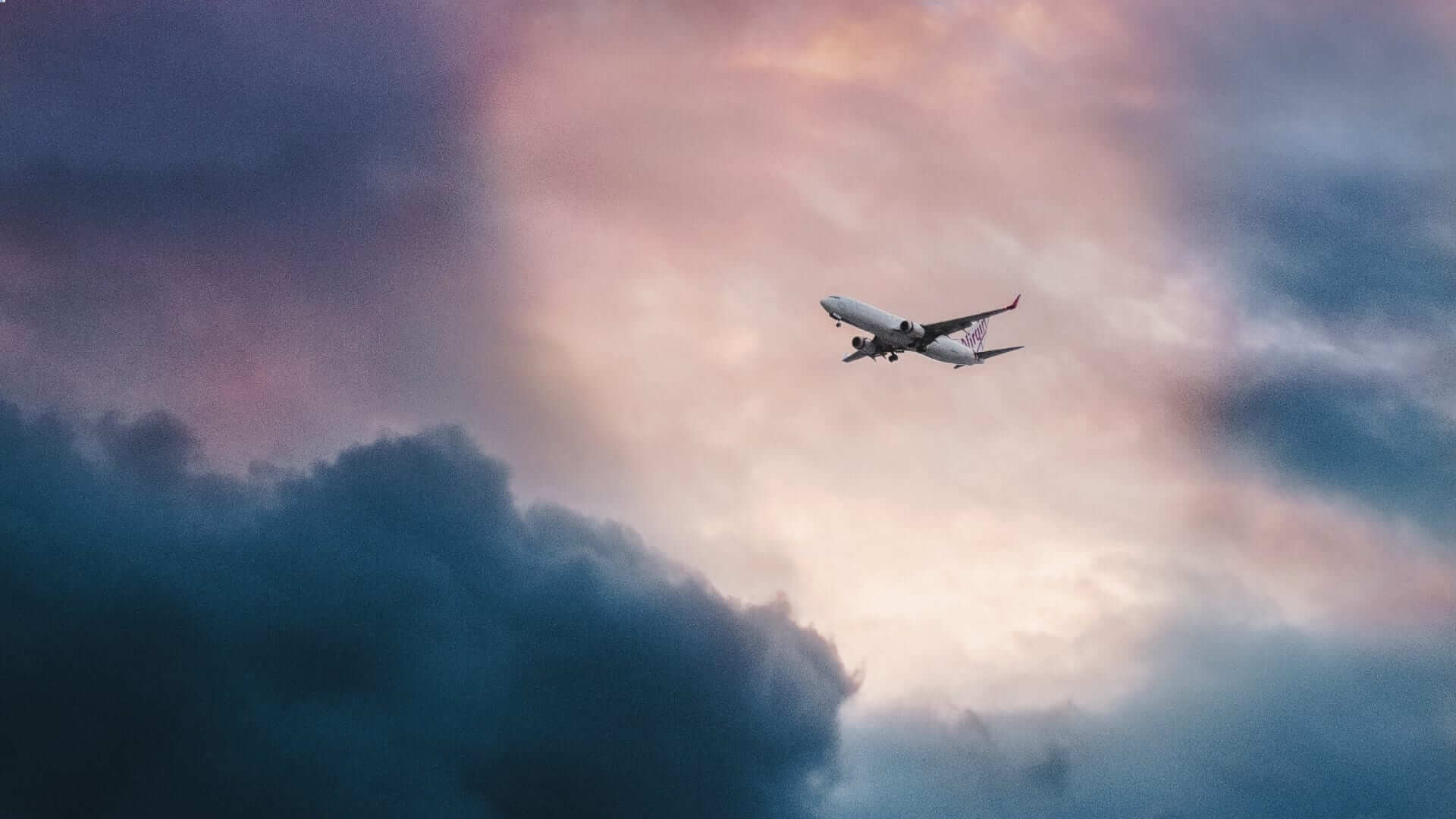 An airplane is flying under pink clouds.
