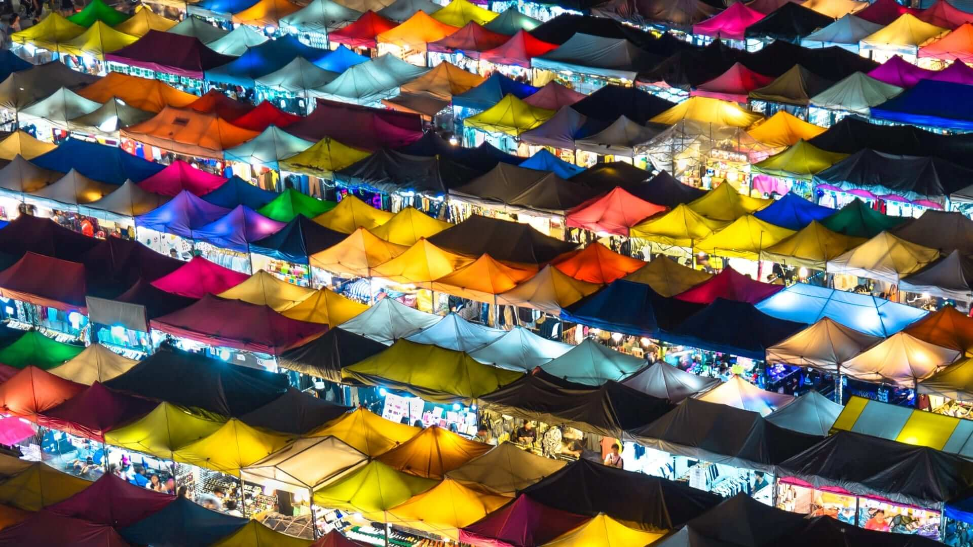 Many colored stalls are standing next to each other during a night in Bangkok.