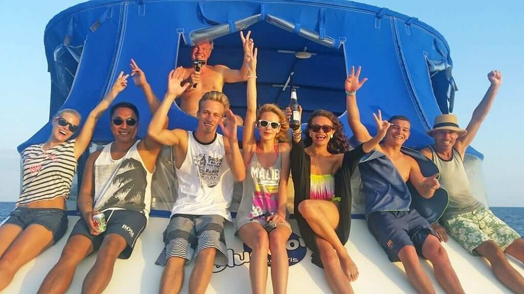 group of people are relaxing on the boat with sun glasses and blue roof
