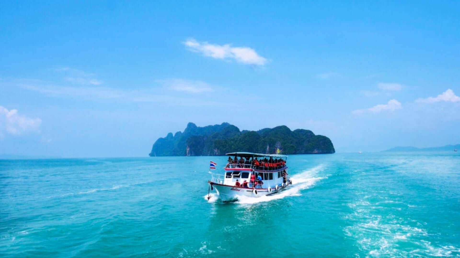 A boat with tourists is sailing on a light blue sea towards an island in Thailand.