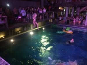 a girl jumping from above to dive in the pool