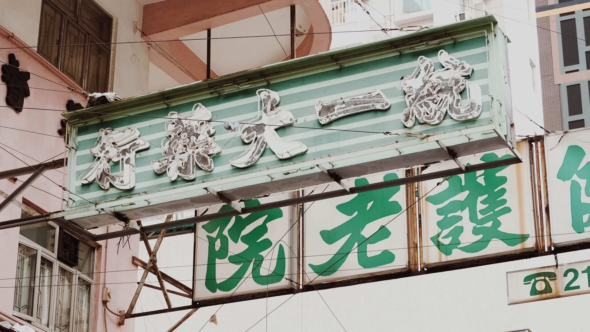Green and white Chinese characters on a building in China.