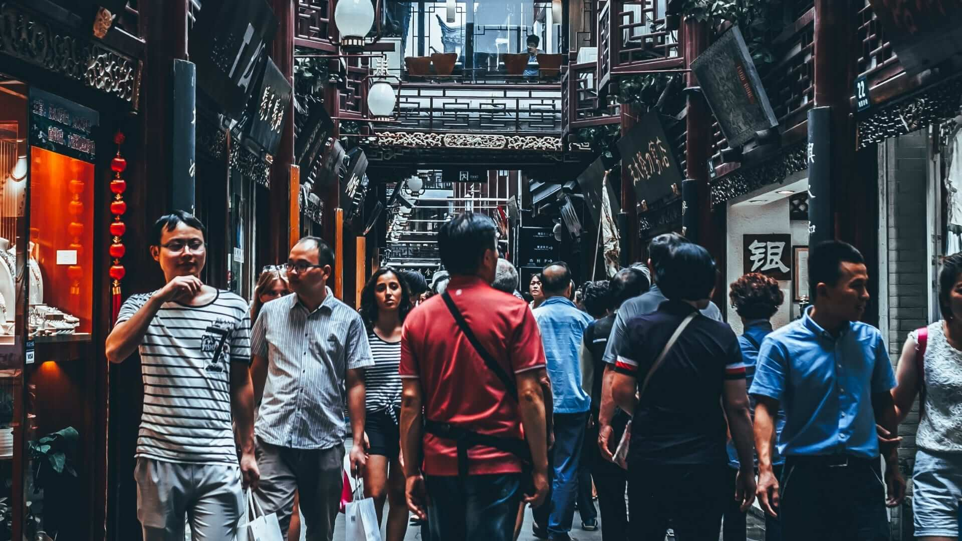 People are walking through a busy street in China.