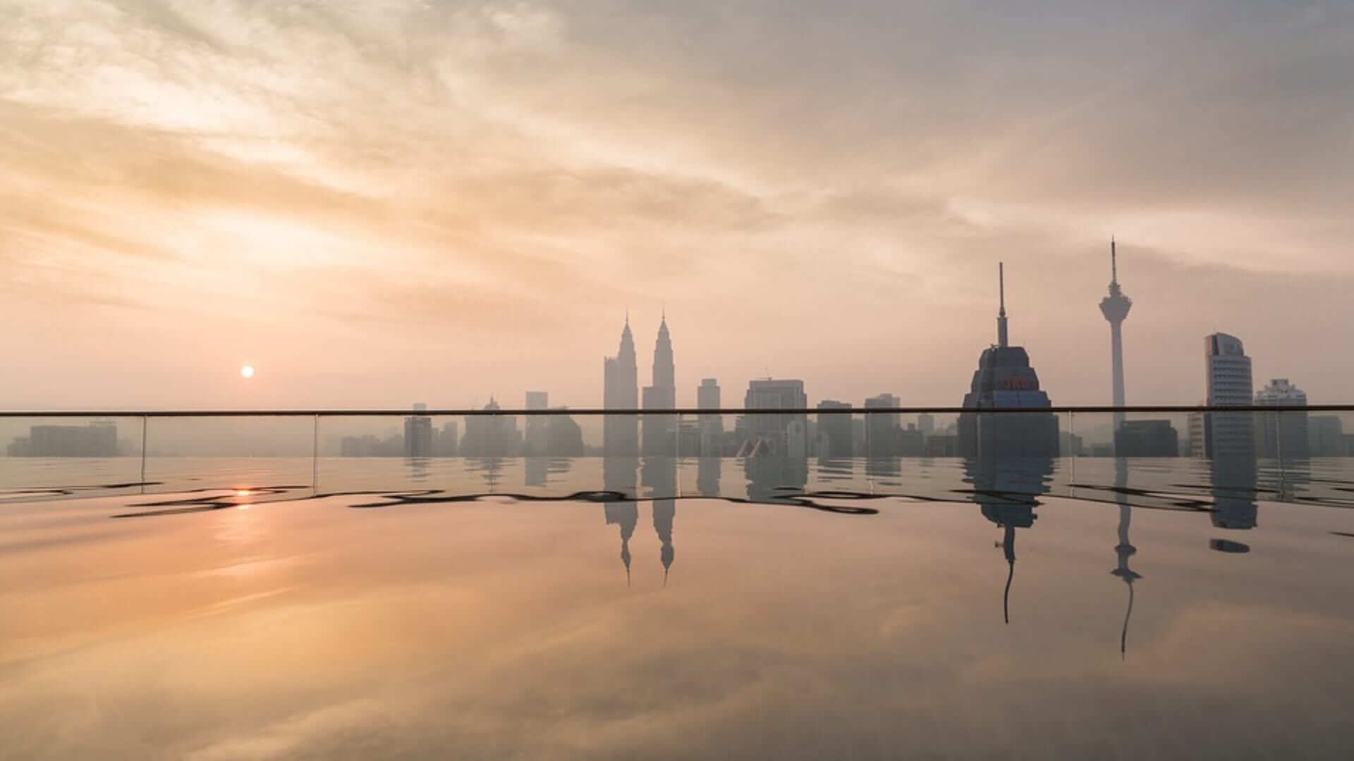 A sky pool during sunset with a view of buildings in Kuala Lumpur.
