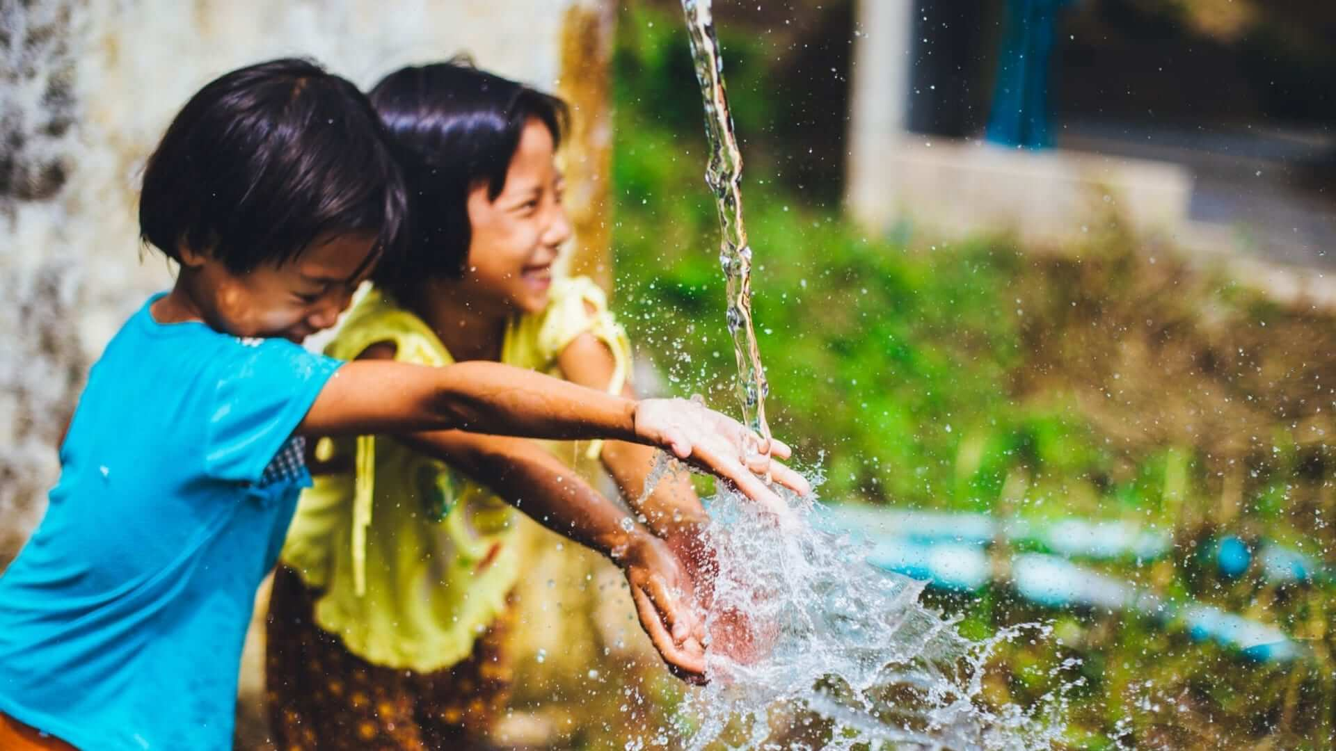 Two smiling children are holding up their hands under a jet of water in Thailand.