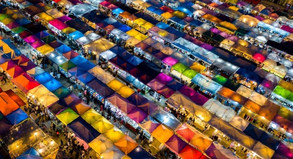 Multiple colourful food vendor stalls next to each other.