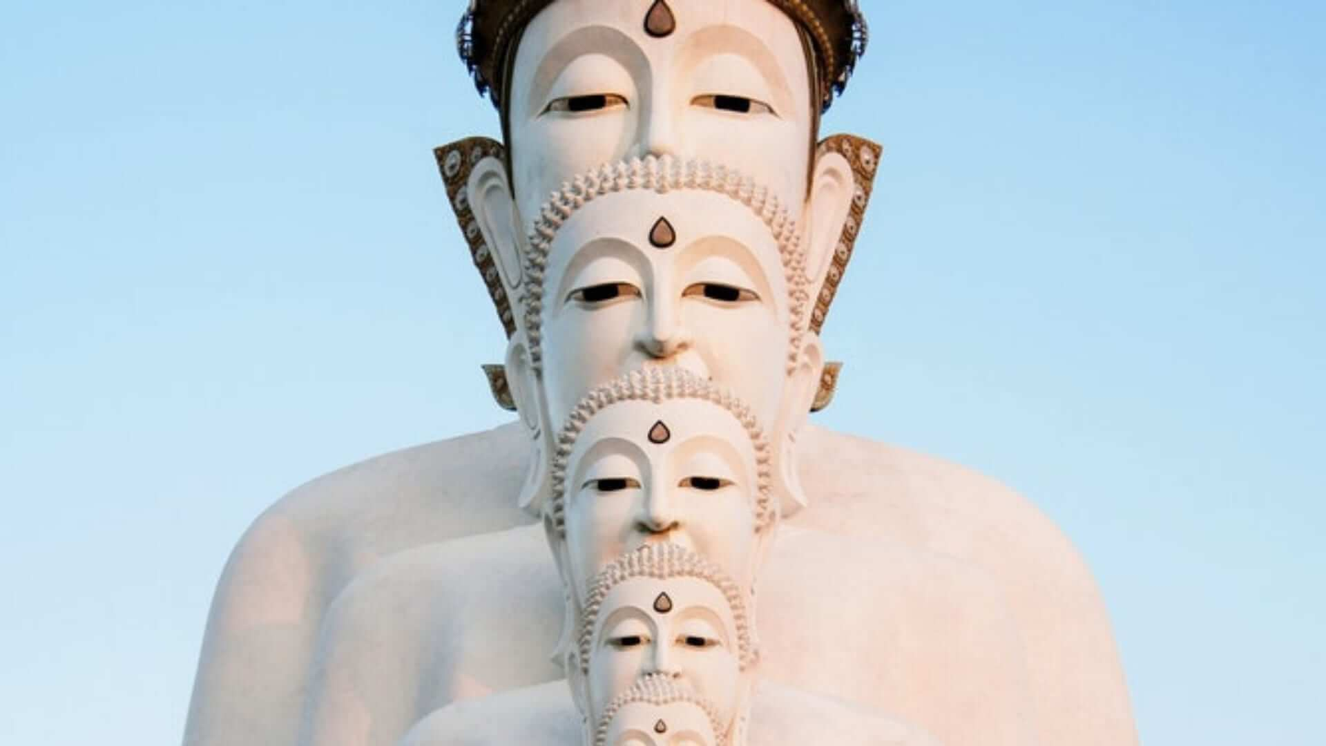 A white statue with five buddha heads on top of each other in Thailand.