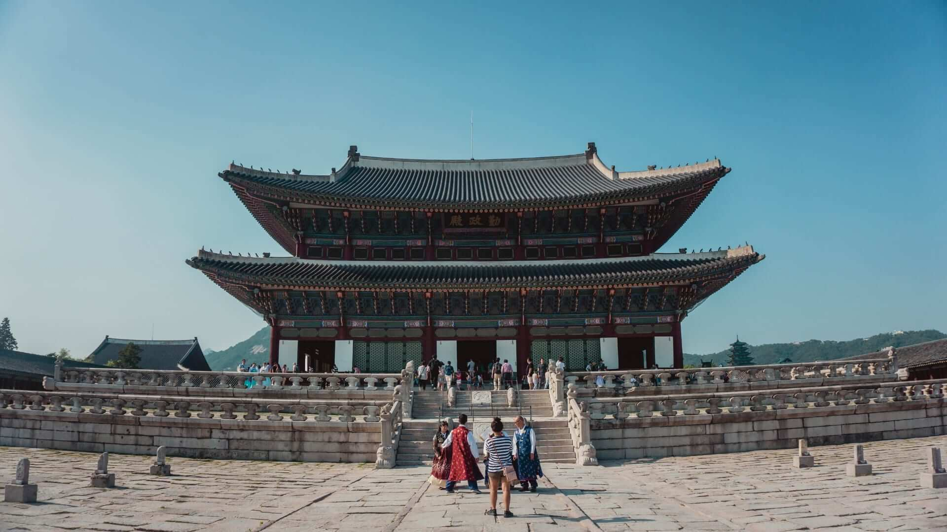 People are standing in front of a colorful temple in South-Korea.