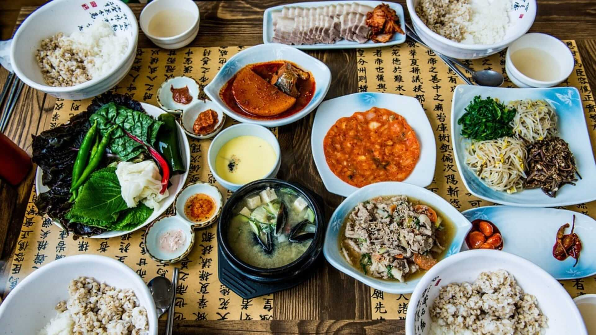 Many different plates with Korean food are laying on a table with Korean characters on it in Seoul.