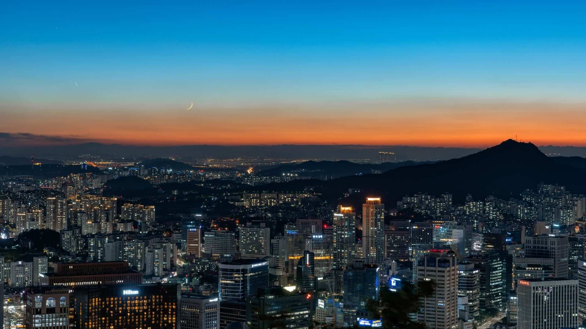 High illuminated buildings in front of a mountain during sunset in Seoul.
