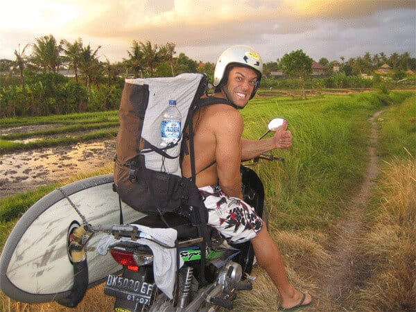 guy have everything on his motorbyke, aqua bottle, surfboard, helmet and smile